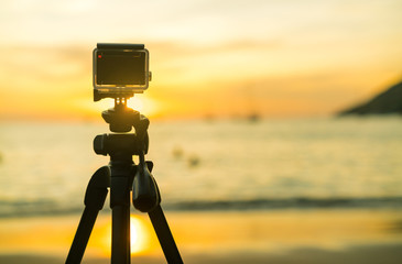 Action Compact camera on a tripod takes photos and videos beautiful sunset over the sea. Taymlaps.