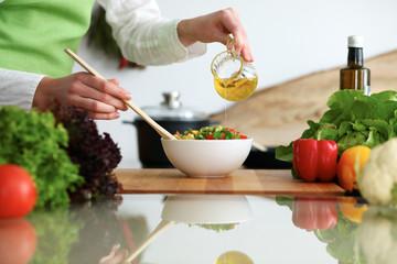 Close-up van menselijke handen die groentensalade in keuken op de glassrlijst met bezinning koken. Gezonde maaltijd en vegetarisch concept