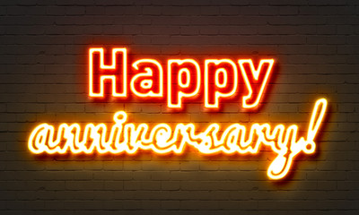 Happy anniversary neon sign on brick wall background.