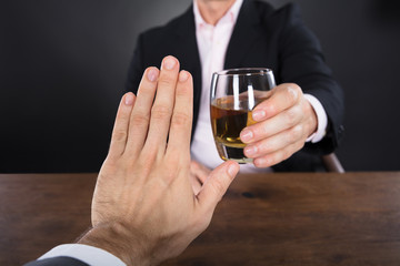 Businessman Hand Rejecting A Glass Of Whiskey