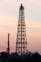 Silhouette oil refinery tower at sunrise