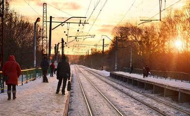 Photo of bright and beautiful sunset on a cloudy sky in cold winter season. Railway track with platforms for waiting trains and power transmission lines in the middle of winter forest landscape