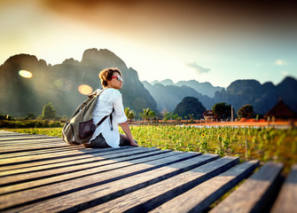 Happy tourist woman meets a sunset overlooking the mountains and fields. Travelling in Asia