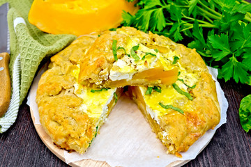 Pie of pumpkin and cheese with parsley on board