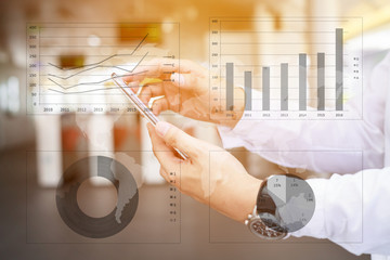 Asia business man hand touch screen on smartphone and business graph background.