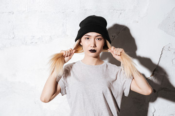 Serious Hipster in black hat holding her hair