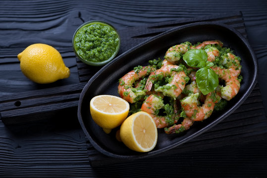 Pan with tiger shrimps in parsley sauce, black wooden background
