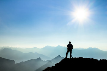 Man reaching summit enjoying freedom and watching towards mountain ranges. Wall mural