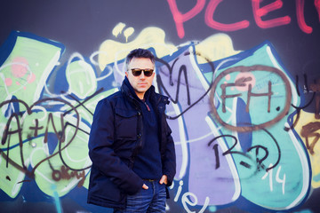 Handsome happy smiling man. Outdoor winter male portrait. Attractive confident middle-aged man in sunglasses posing in city park over grunge abstract art graffiti wall, image toned and noise added.