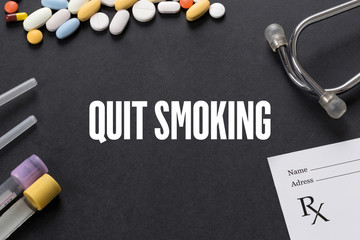 QUIT SMOKING written on black background with medication