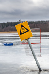 Yellow warning sign and hockey goal on wet melting ice on frozen lake, Sweden.