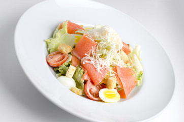 Salad with marinated salmon on a white plate