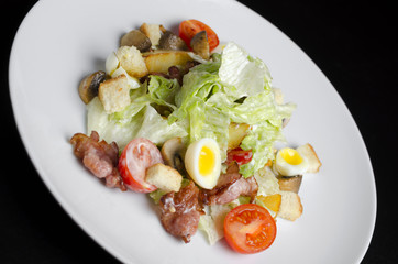 Salad with fried bacon and vegetables on a white plate on a black background
