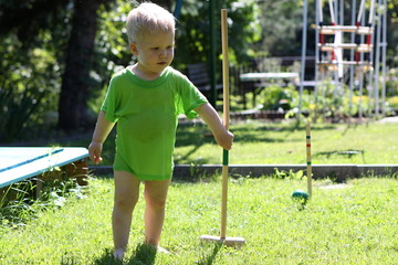 Little boy in wet green shirt playing polo