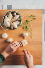 Man cutting fresh mushrooms on a wooden cutting board