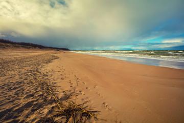 Sea shore. Cloudy sky and blue ocean. Beach in autumn