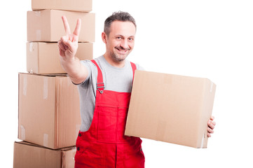 Smiling mover man holding cardboard box and showing peace