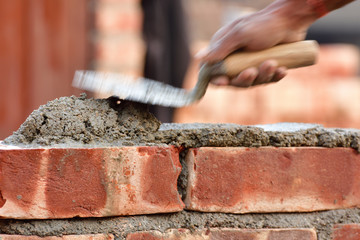 To build up a brick wall with trowel