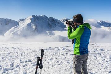Tourist does photo camera, winter mountain scenery.