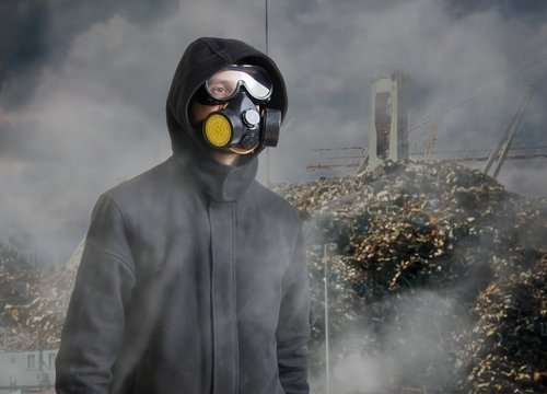 Pollution and toxic waste concept. Man with gas mask in front of landfill.
