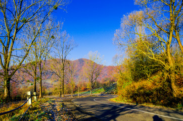 autumn landscape, the road leading into the mountains, blue mountains in the fog in the background.