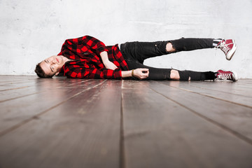 Hipster in shirt lying on the floor