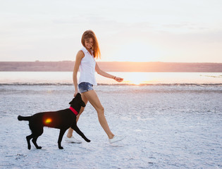 Young female walking with labrador retriever dog on the beach at sunset