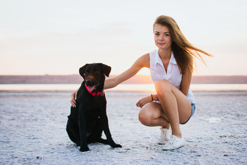 Young female hugging with labrador retriever dog on the beach at sunset