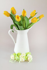 Yellow garden tulips in jug with easter eggs