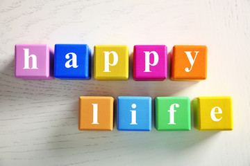 Colorful cubes with text HAPPY LIFE on wooden background