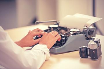 Journalist typing on retro machine, closeup