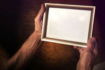 Old man holding and looking at photo frame