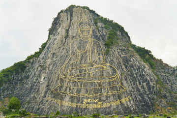 Golden huge buddha statue on the hillside of large mountain in touristic park