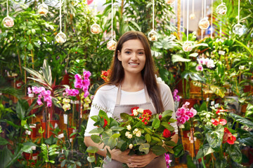 Pretty young florist with beautiful bouquet in greenhouse