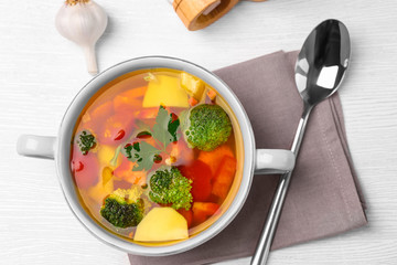 Saucepan with vegetables soup on kitchen table