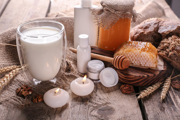 Milk, honey and cosmetic on wooden background
