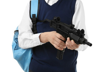Schoolboy holding machine gun on white background