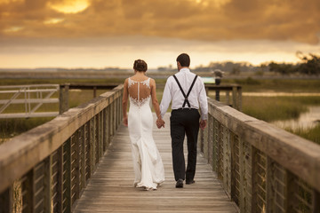 Beautiful newly married couple walking away with dramatic sky