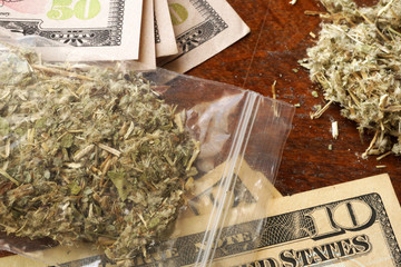 Bag of marijuana or weed on dollars. Drug trading concept.