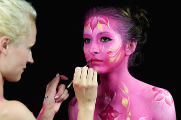 Bodypaint master in work, paints a model for a photo shoot