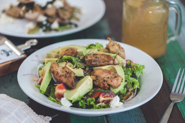 Fresh salad with chicken, tomatoes and avocado close up.