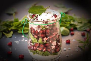Glas mit Granatapfelkernen und jungen Spinat