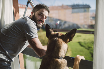 Young man standing at window with his dog, waiting