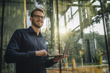Smiling businessman using laptop in lobby
