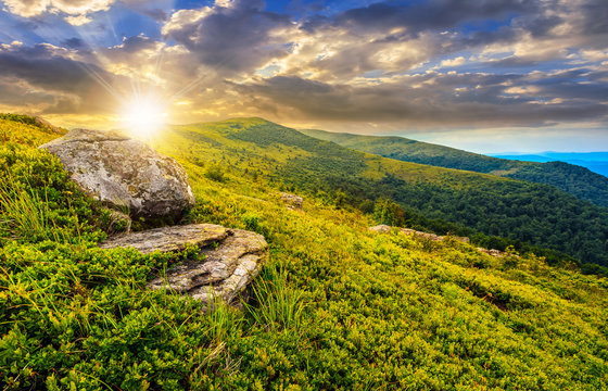 meadow with boulders in Carpathian mountains in summer at sunrise