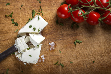 Feta cheese with knife and bunch of cherry tomatoes