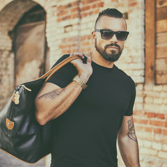 Handsome man with beard wearing sunglasses and holding black bag