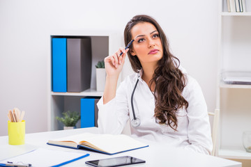 Beautiful female doctor thinking while working at her office.