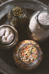Beans, lentils, rice in a glass jar on a plate