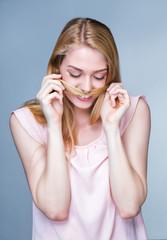 Portrait d'une jeune femme souriante, les cheveux devant la bouche / Portrait of a smiling young woman, hair in front of the mouth